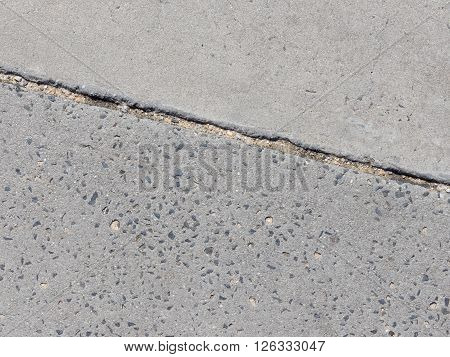 Old gray concrete surface with depressed gravel and the gray concrete decorative surface and expansion joint between them on the track to the street
