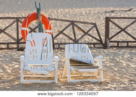 Two Old Beach Chairs Stand Near The Lifeline On The Sandy Beach