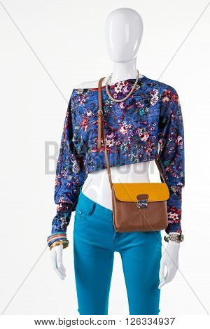 Floral crop top and purse. Stylish bicolor bag on mannequin. Girl's outfit with leather handbag. Accessory sale in outlet store.