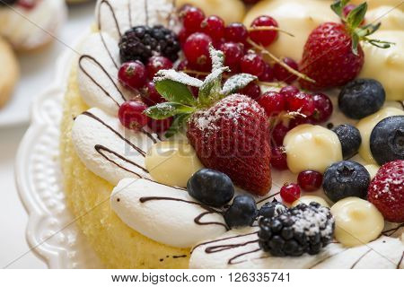 cake pastry decorated with fresh fruits and cream, closeup