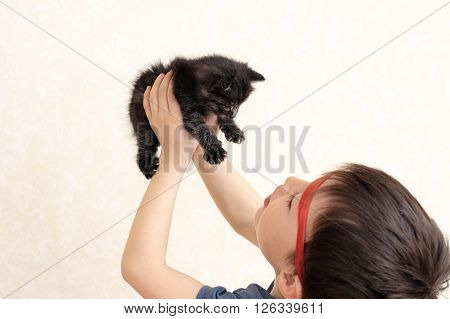 Caucasian boy holding up black kitten and playing