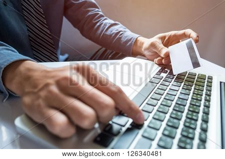 Man holding credit card in hand and entering security code using smart phone on laptop keyboard online shopping concept.