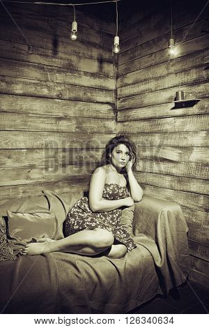Redhead girl in red dress sitting on a couch over wooden background