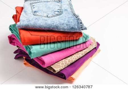 A stack of colored jeans on white background