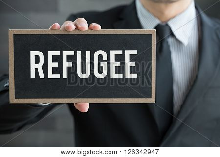 Refugee message on blackboard and hold by businessman