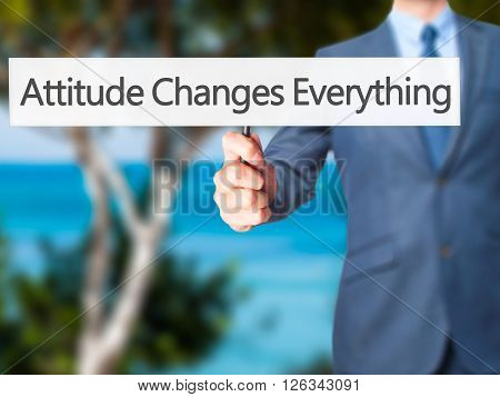 Attitude Changes Everything - Businessman Hand Holding Sign