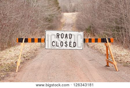 Road closed sign on rural unpaved road.