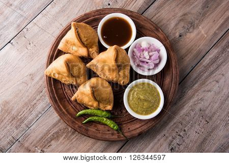 samosa snack with imli chutney or tamarind sauce, onion and green fried chili, served on wooden plate