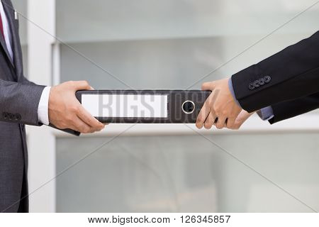Businessman delivering documents to businessman in office