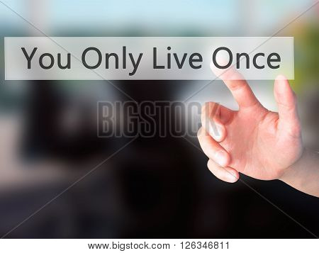 You Only Live Once - Hand Pressing A Button On Blurred Background Concept On Visual Screen.
