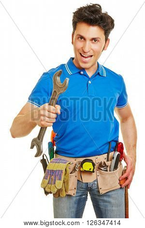 Smiling handyman holding a wrench and carrying a tool belt