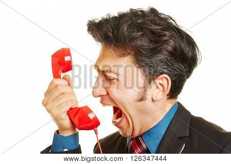 Angry business man screaming loudly into a red phone receiver