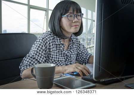 45s years woman working in front of computer monitor office life theme