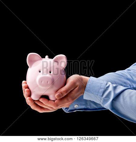 man's hands hold classic piggybank