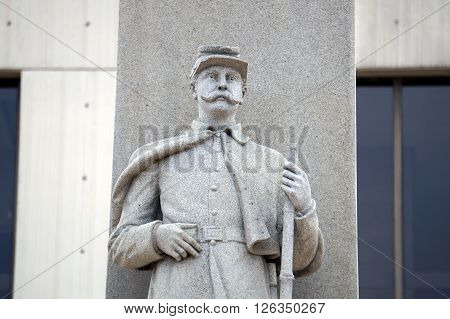 A figure of a Union Army soldier officer holding a rifle stands on the Will County Civil War Memorial, aka the Soldiers and Sailors of Civil War Monument, erected in front of the Will County Courthouse in Joliet, Illinois in 1884.