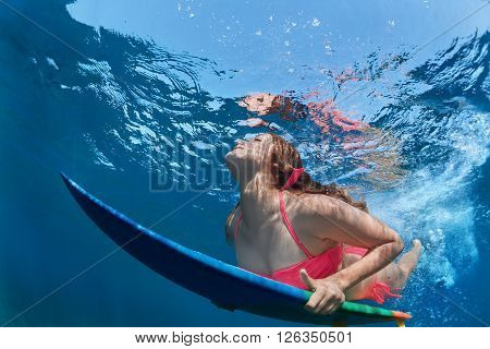 Young girl in bikini in action - surfer with surf board dive underwater with fun under big ocean wave. Family lifestyle people water sport lessons beach extreme swimming activity on summer vacation