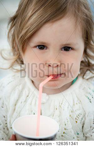 Cute little girl drinking milk using drinking straw