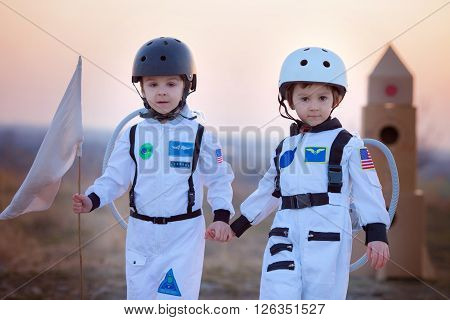 Two Adorable Children, Playing In Park On Sunset, Dressed Like Astronauts