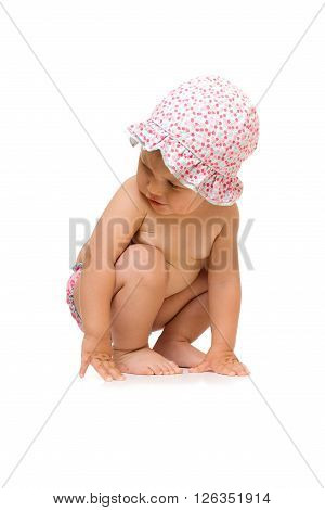 Little child sitting in sunhat, isolated over white