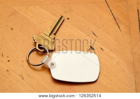 Keyring With Key And White Fob On Wood Table