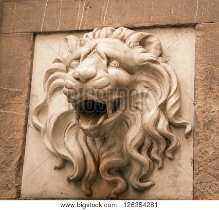 Statue of lion's head on a wall in florence italy
