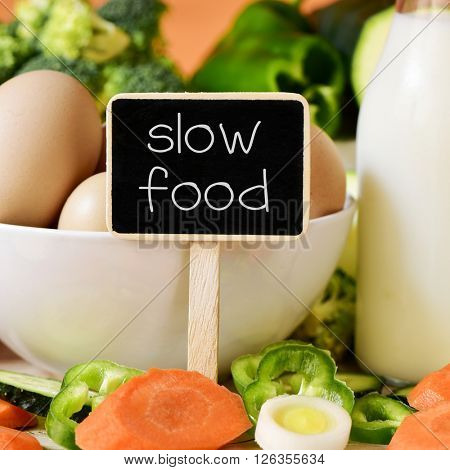 closeup of a signboard with the text slow food on a table full of different raw vegetables, a bowl with some chicken eggs and a bottle with milk