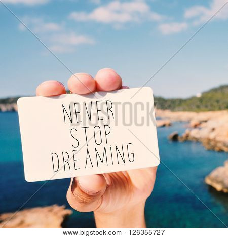 closeup of the hand of a young man with a signboard with the text never stop dreaming, with the sea in the background