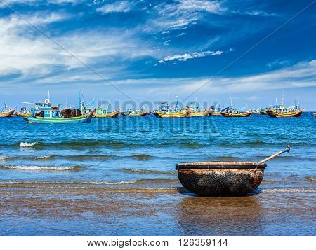 Coracle and fishing boats on beach in Mui Ne, Phan Tiet, Vietnam