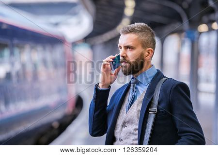Hipster businessman with smartphone, making a phone call, walking at the train station platform