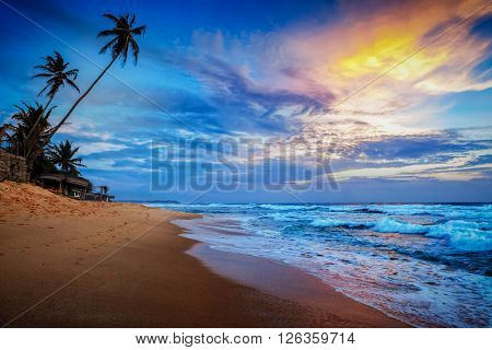 Beach holidays vacation romantic concept background - sunset on tropical beach with dramatic cloud sky. Sri Lanka