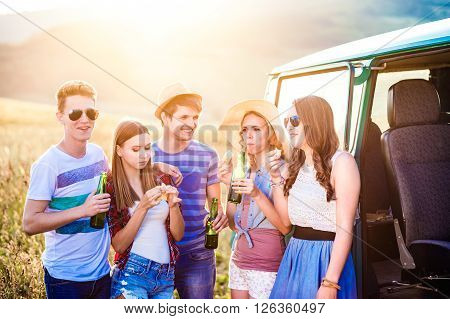 Group of teenage hipsters on a roadtrip, drinking beer, eating. Young friends outside on a summer day.