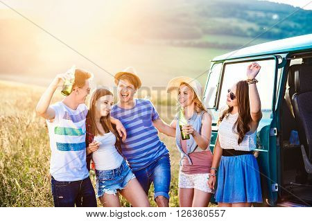 Group of teenage hipsters on a roadtrip, drinking beer. Young friends outside on a summer day.