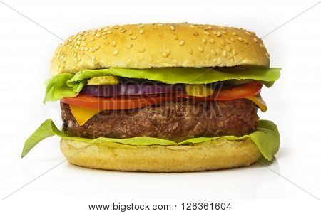 A photo of a burger with leaves of green lettuce slices of Cheddar cheese gherkins red onions tomatoes and a thick meat patty isolated on white