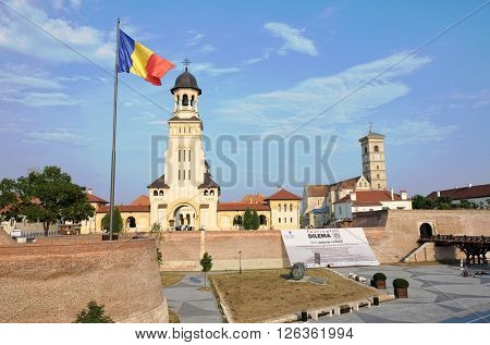 ALBA IULIA, ROMANIA - AUGUST 11, 2015: the Romanian flag waving on the Coronation Cathedral in Carolina Citadel of Alba Iulia