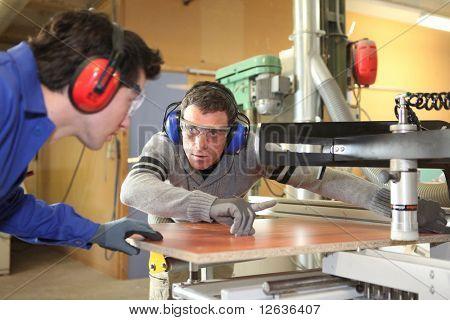 Carpenter and apprentice working in studio