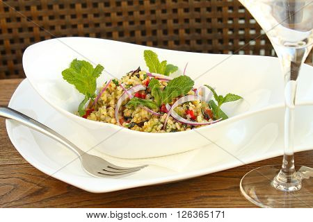 bulgur with vegetables in white plate on a dark wooden background