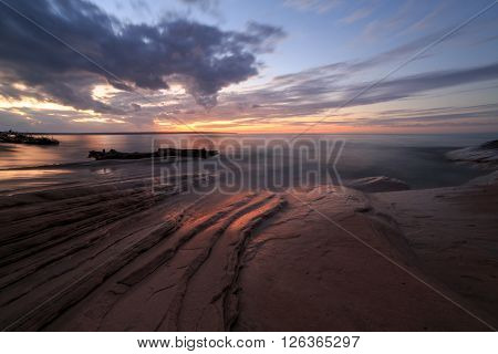 Sunset at Miners Beach in the Upper Peninsula of Michigan. Miners Beach is part of Pictured Rocks National Lakeshore near Munising Michigan