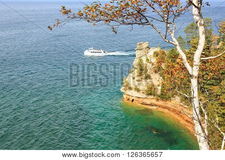 Munising, Michigan, United States, OCTOBER 10, 2015: A ferry boat carrying tourists passes Miners Castle at Pictured Rocks National Lakeshore in the Upper Peninsula of Michigan