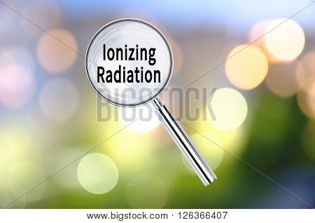 Magnifying lens over background with text Ionizing Radiation, with the blurred lights visible in the background. 3d Rendering.
