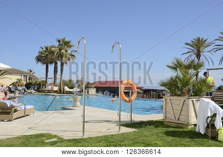 MARBELLA, SPAIN - APRIL 9, 2016: Some people refreshing and sunbathing at a pool in a a beach club in Marbella Spain.