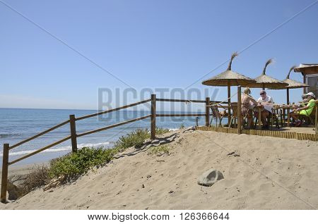 MARBELLA, SPAIN - APRIL 9, 2016: People having lunch at sun in the terrace of a beach bar in spring in Marbella a city in southern Spain belonging to the province of Malaga Andalusia Spain