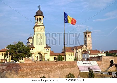 ALBA IULIA, ROMANIA - AUGUST 11, 2015: the Romanian flag waving between the Orthodox Coronation Cathedral  and St. Michael Roman Catholic Cathedral in Carolina Citadel of Alba Iulia