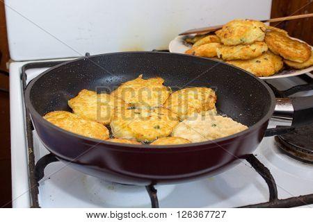 Golden fried potato latkes in a cast iron skillet