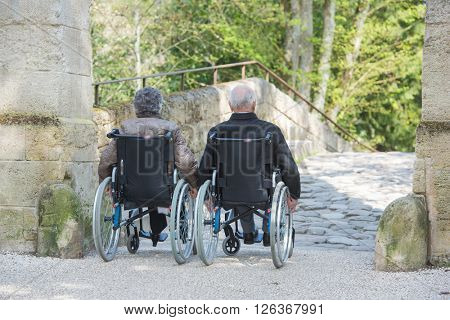 Elderly couple in wheelchairs