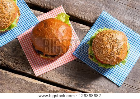 Burgers with lettuce and sesame. Wooden table with delicious burgers. Junk food in old diner. Wake the appetite up.