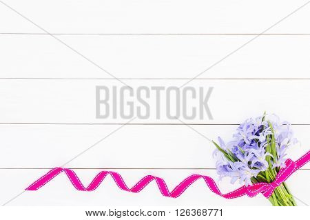Bouquet Of Spring Flowers Decorated With Ribbon On White Wooden Background. Top View, Copy Space. Ch