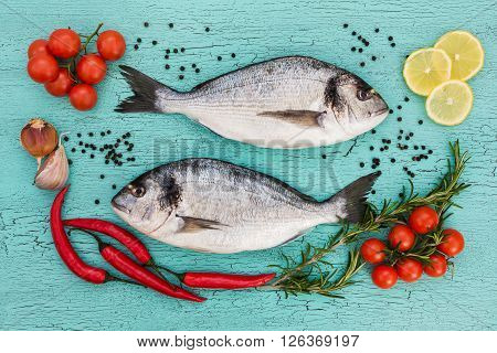 Raw Dorado Fish With Vegetables On Blue Background. Top View