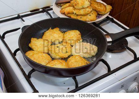 fried potato pancakes on a hot pan on a gas stove
