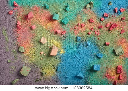 Powder and pieces of colored chalk. Natural close-up detailed color texture for background.