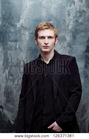 young man in the jacket thoughtfully looks into the camera